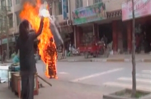 A woman throws a white scarf over Tibetan Buddhist nun Palden Choetso as she burns on the street in Daofu, or Tawu in Tibetan, in this still image taken from video